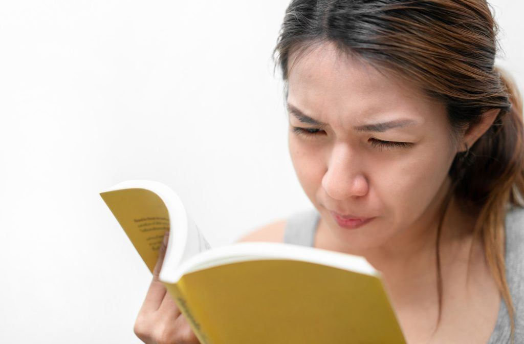 Young woman with myopia squinting while holding book near face