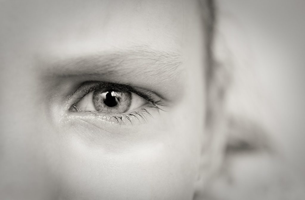 Black and white close-up of child with one dilated eye