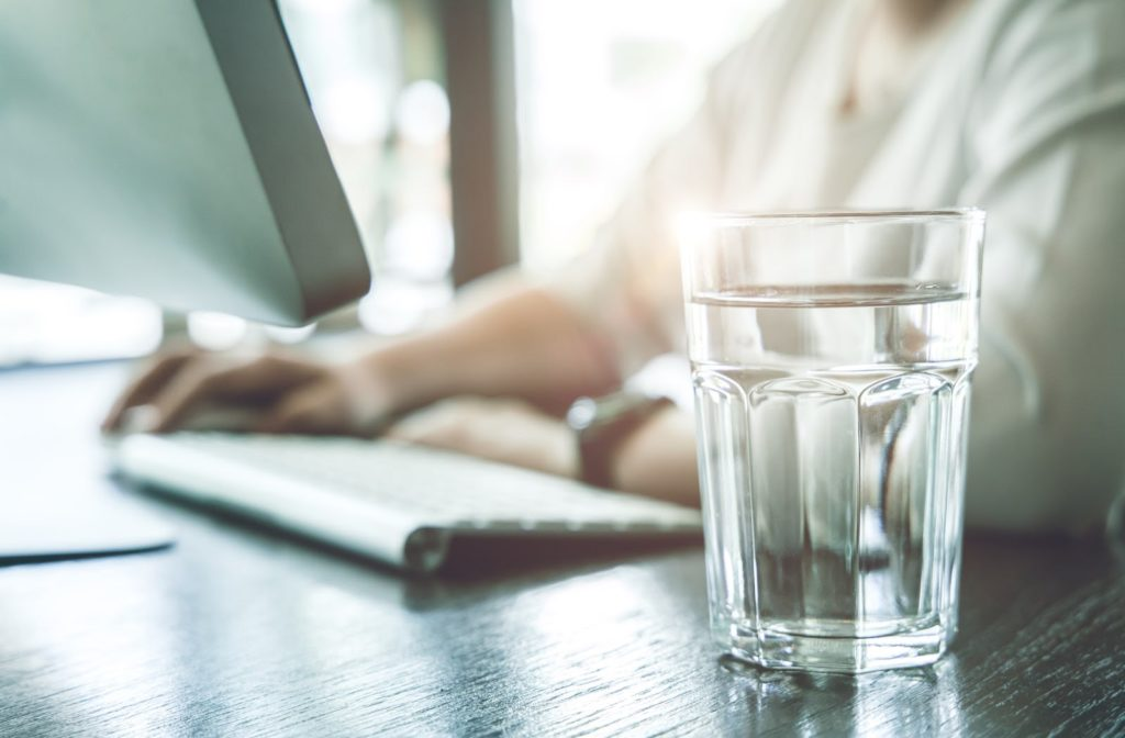A glass of water placed on a desk near a woman