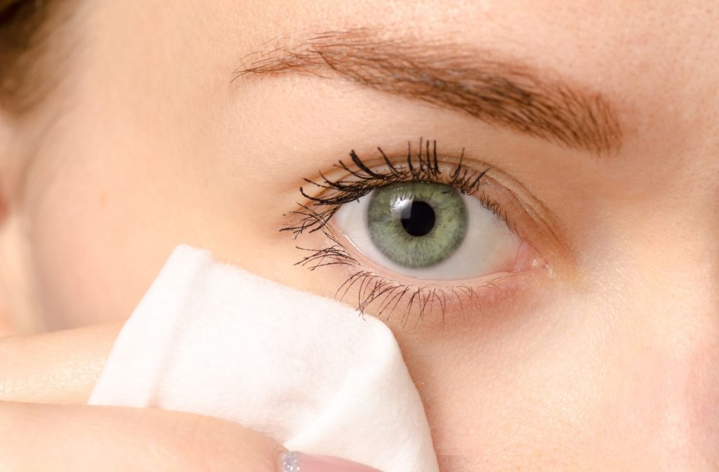 Woman with green eyes uses makeup removal wipes to wipe her eyes