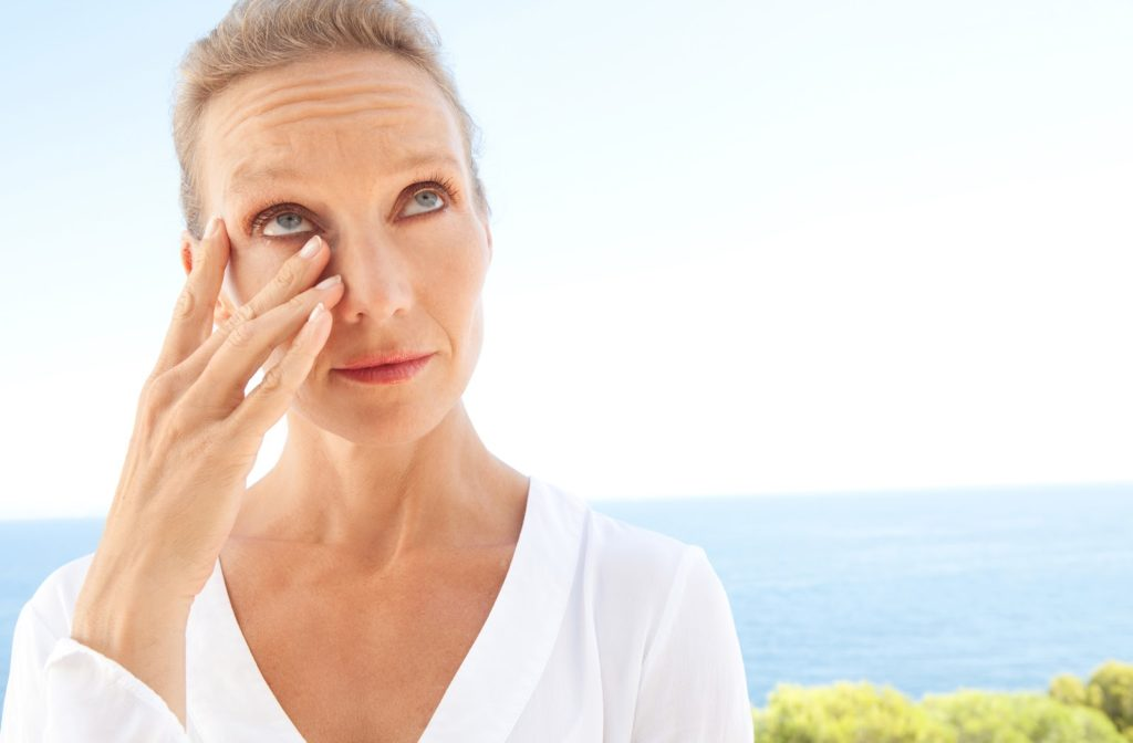 Woman touching her irritated eye due to dry eye caused by makeup.