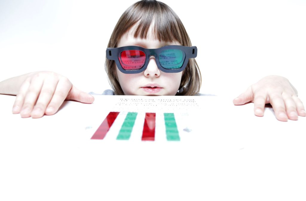 Child with red and green reading bars and glasses during vision therapy.