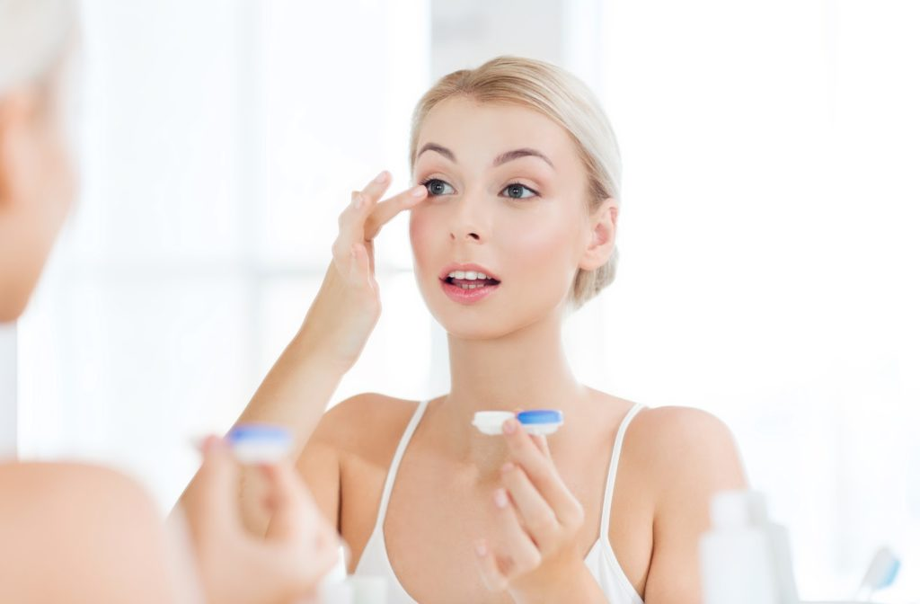Young woman wearing contact lenses while looking in the mirror.