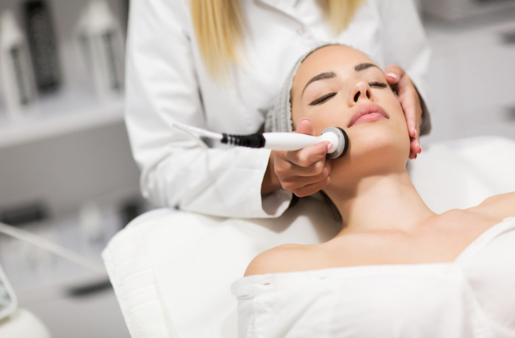 Young woman receiving radio frequency skin tightening treatment from professional